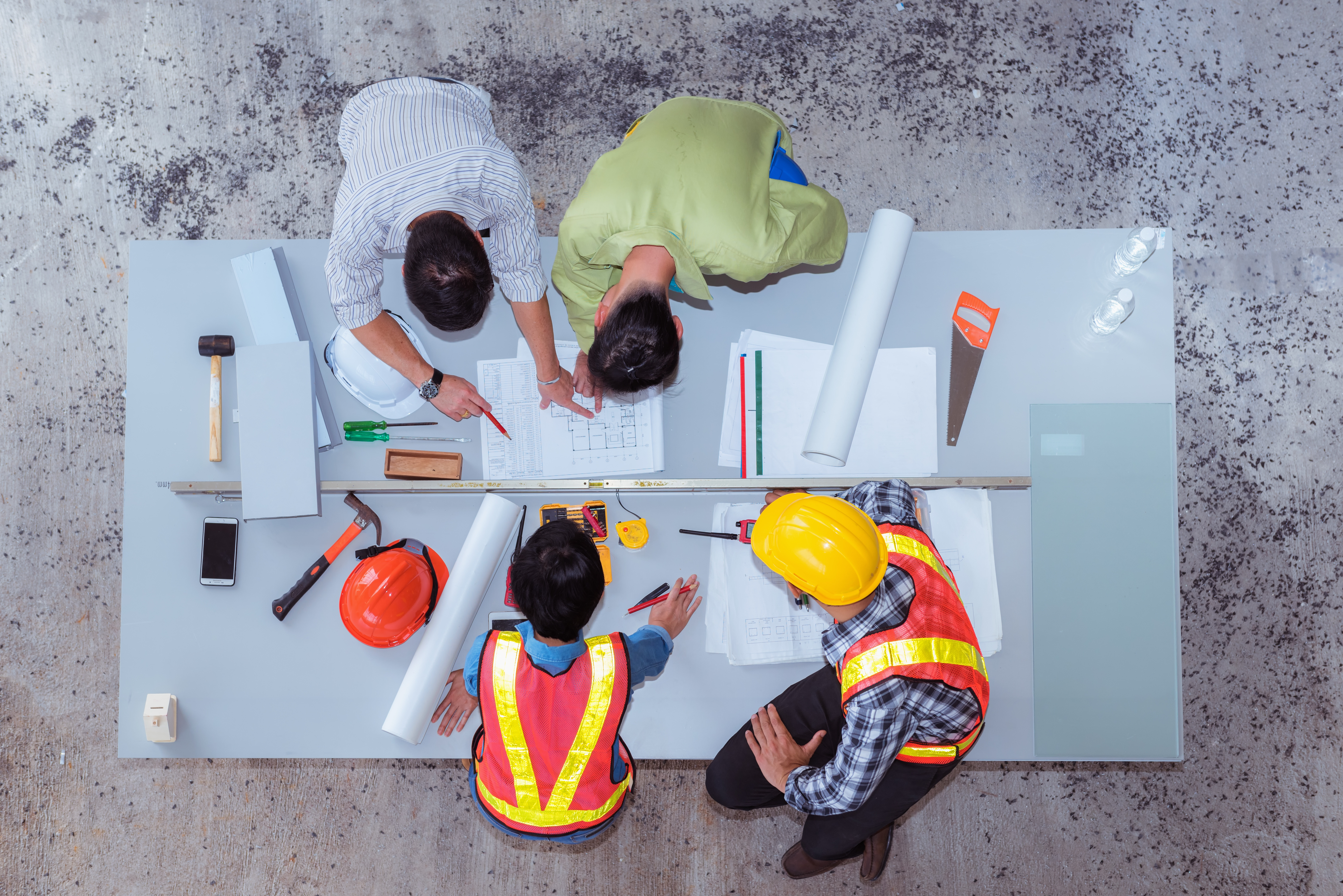 overhead view of construction workers planning at a table