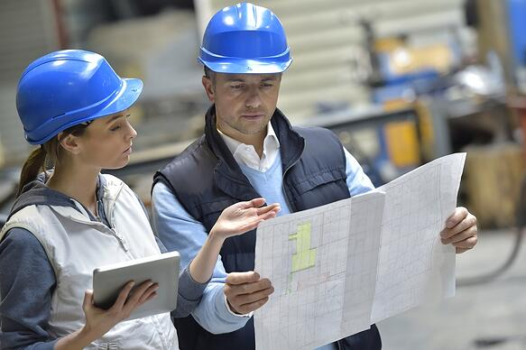 Engineers in hard hats reading blueprints in factory