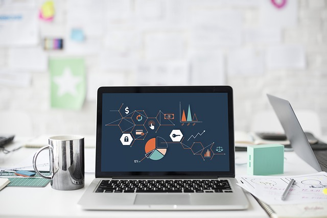 laptop with visual charts and graphics on office desk