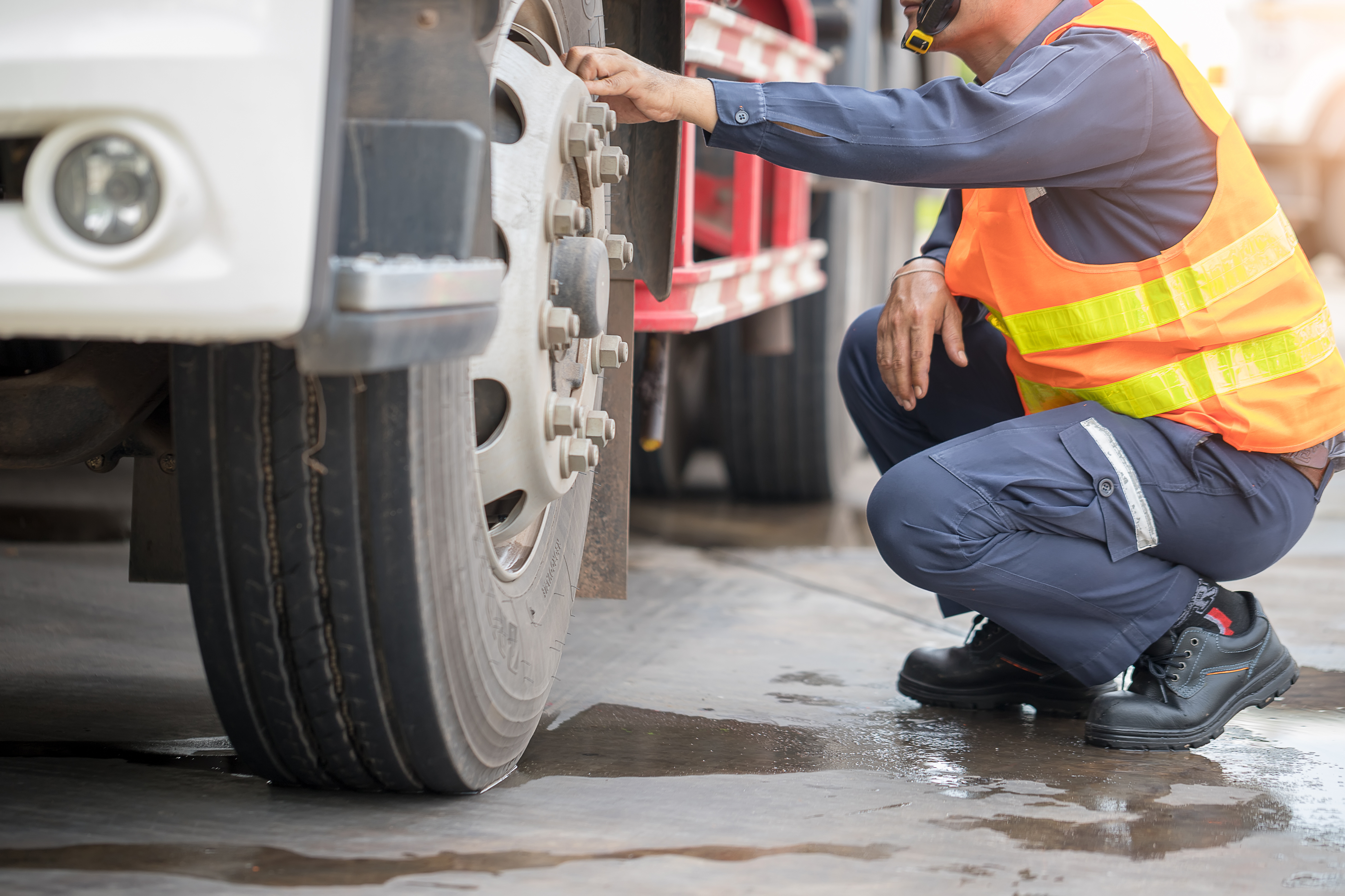 Commerical driver inspecting truck tire during daily vehicle inspection report