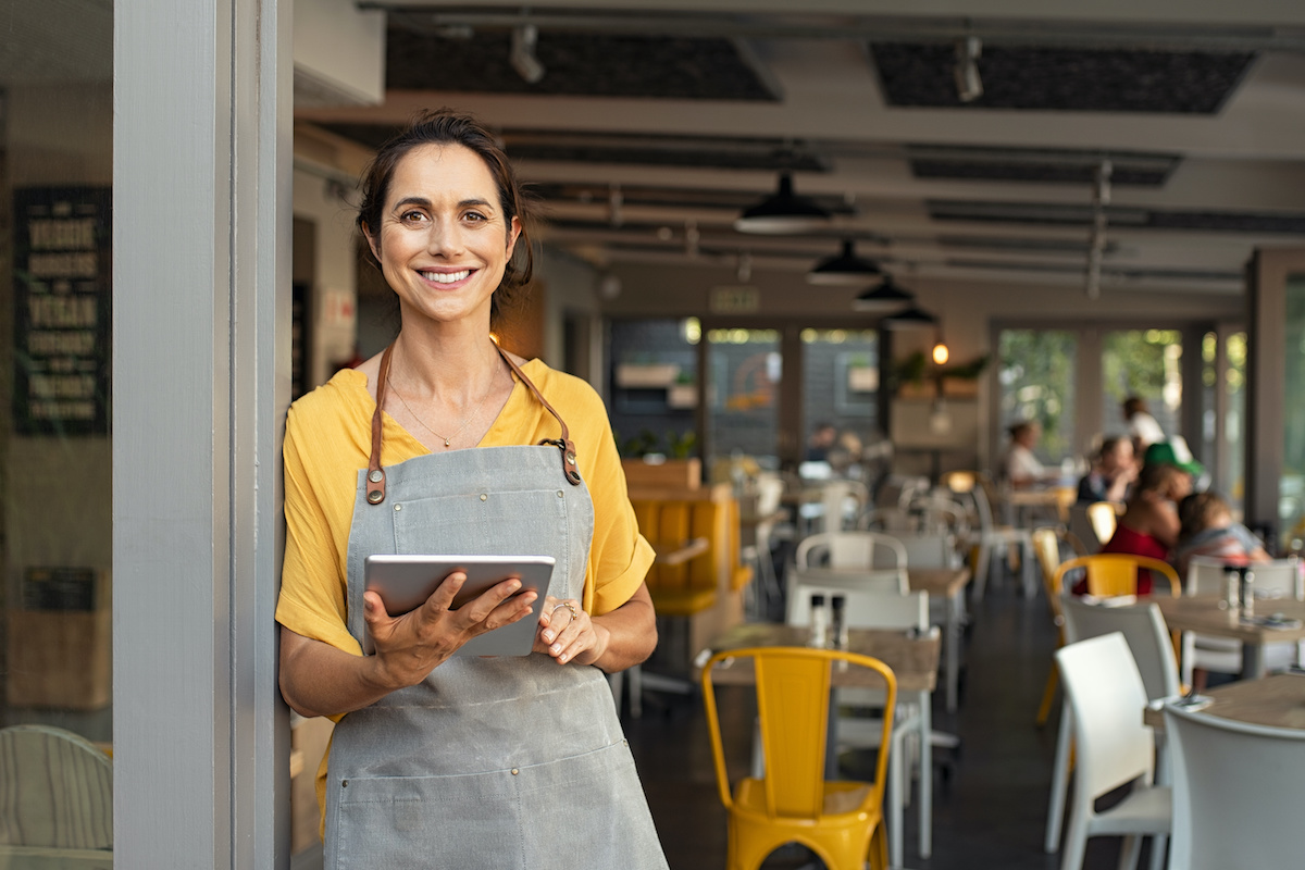 restaurant employee in cafe with digital restaurant inspection checklist app on tablet
